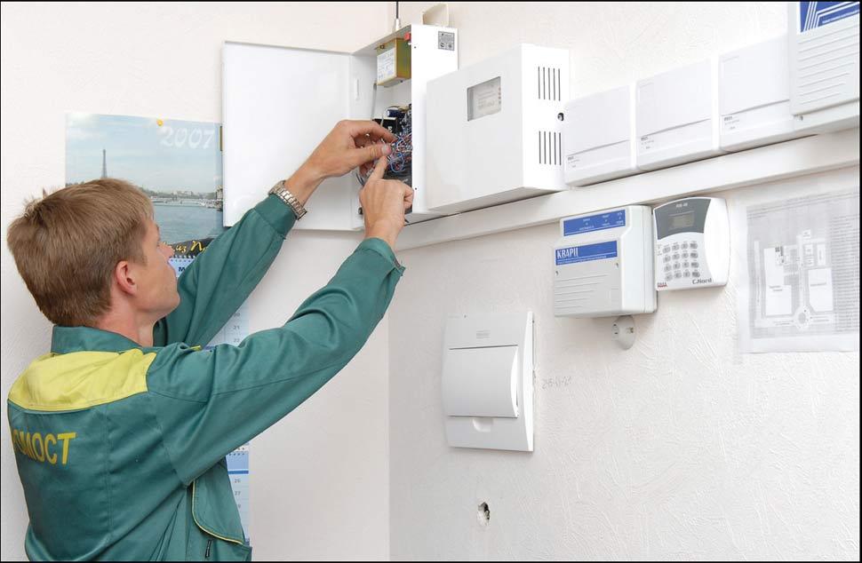 На фото специалист компании устанавливает охранной сигнализацию.